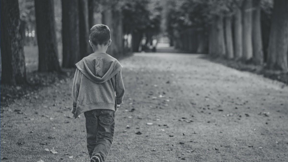 Petit garçon de dos qui marche dans l'allée d'un parc
